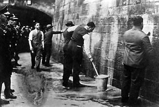 SPD-Politiker werden unter Aufsicht der SA gezwungen, Wandparolen zu entfernen. 1933